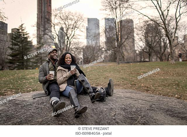 Couple sitting on rock in park with takeaway coffee