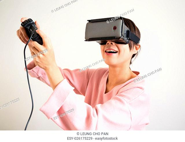Excited woman play with joystick and vr device