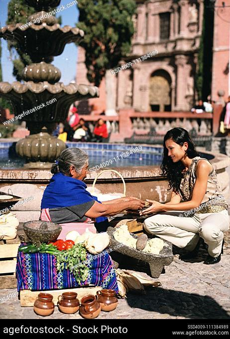 Hispanic woman buying tortilla from street vendor