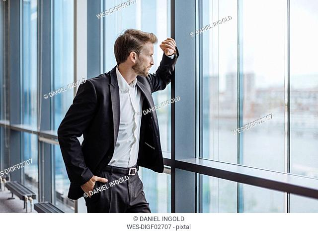 Businessman standing in office looking out of the window