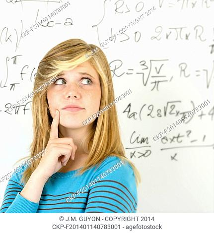 Thinking student teenager standing in front of mathematics board