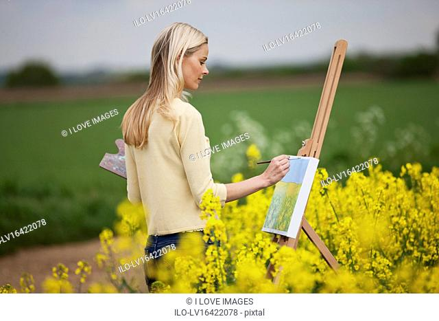 A young woman painting a picture of a rape seed field in flower, side view