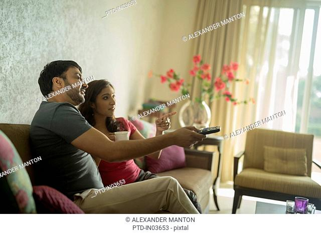 Man and woman on sofa using television remote