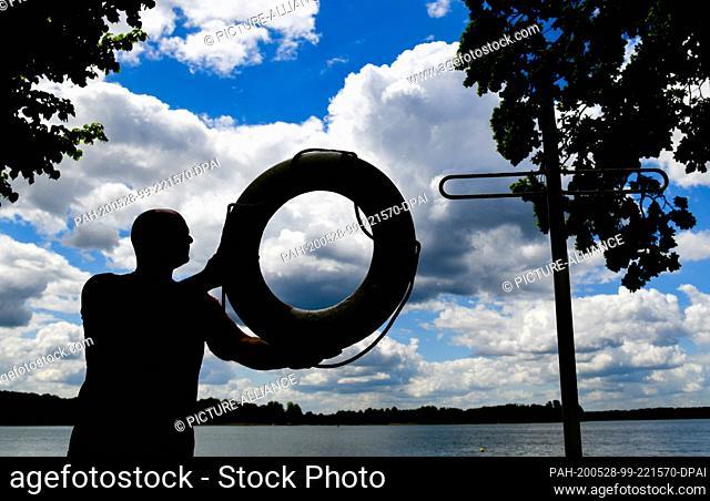 28 May 2020, Brandenburg, Wandlitz: Dennis Kowald, head of the lido at Strandbad Wandlitzsee, installs a life ring on a bracket on the shore of the lake