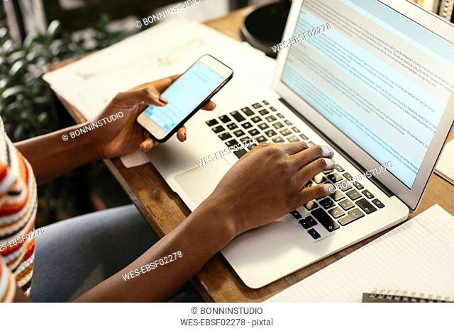 Woman sitting at desk using smartphone and laptop, partial view