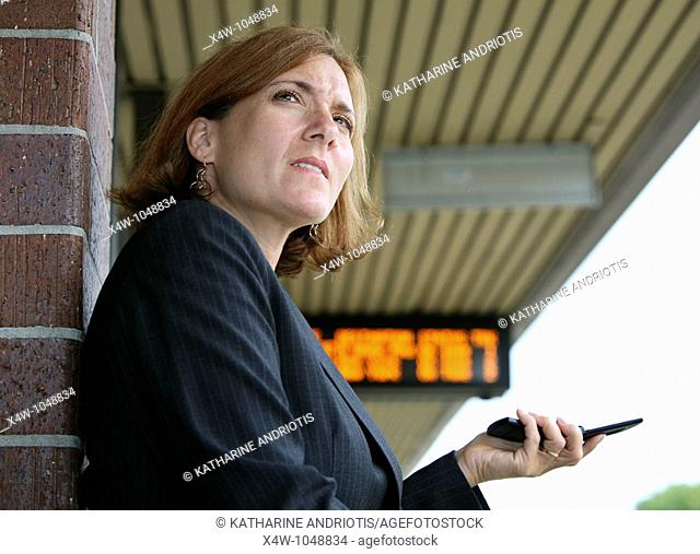 Businesswoman standing on platform hold her cell phone with train timetable in background awaiting the arrival of her commuter train on her way to work