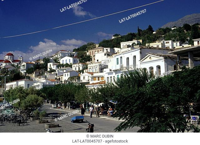North East Aegean islands. Street. Taverna. Awnings. Trees. Houses. Church on hill. People
