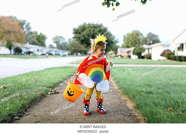 Young girl standing on a pavement, wearing colourful costume with rainbow, sun and clouds, holding orange plastic bucket