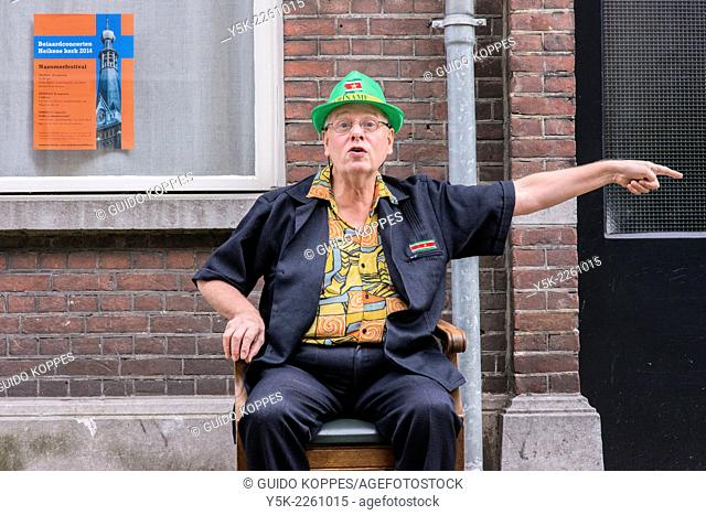 Tilburg, Netherlands. Man sitting in his newly bought chair in front of a facade in the streets and pointing towards a situation at his left