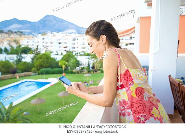 adult woman, with red dress and sunglasses, typing on mobile phone in the terrace. Behind pool, grass and houses