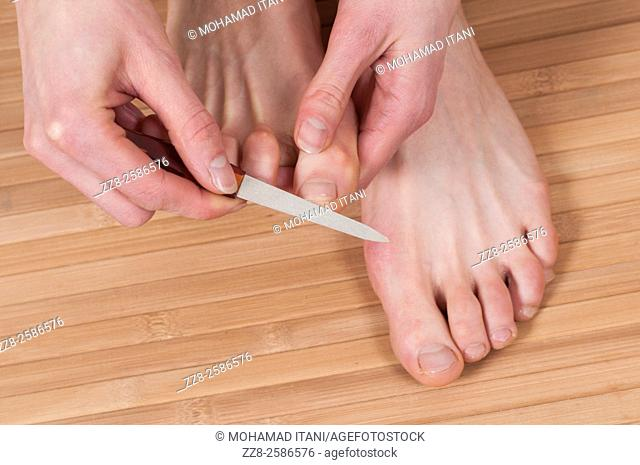 Close up of a young woman giving her feet a pedicure