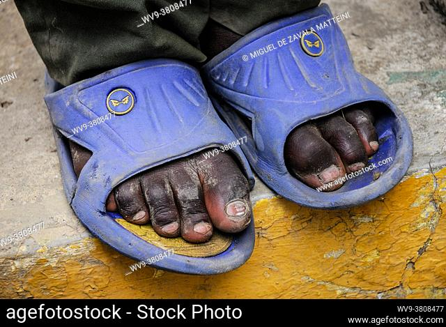 Feet of a young black labourer