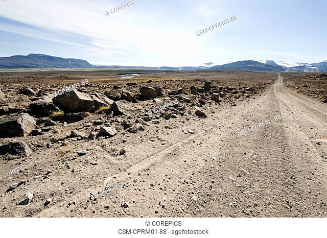 Desert road through the barren, deserted tundra landscape of Central Iceland