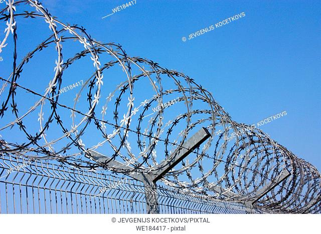 fence with barbed wire against the blue sky. Symbol of freedom of imprisonment