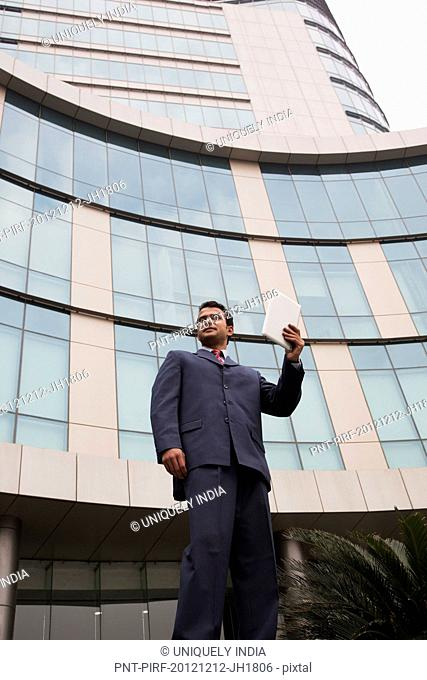 Businessman standing outside an office building with a digital tablet
