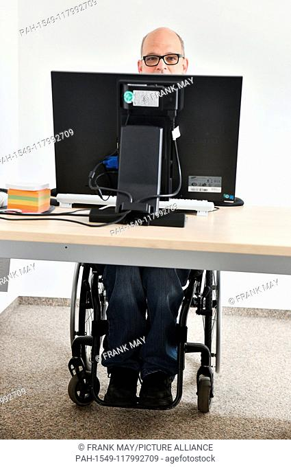 A wheelchair user at his workplace, Germany, city of Hamburg, 05. March 2019. Photo: Frank May (model released) | usage worldwide