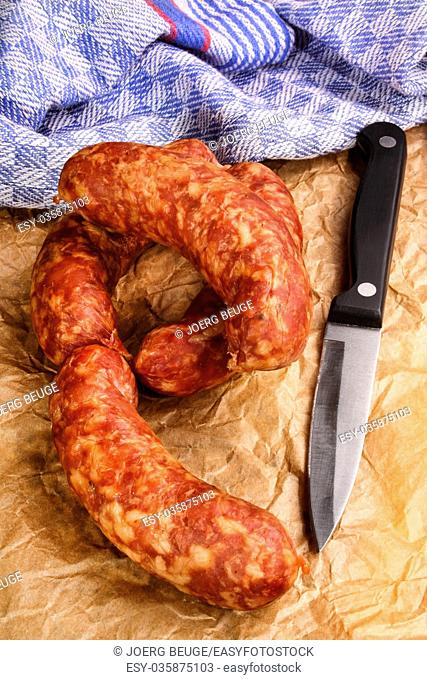 smoked sausage with knife on brown kitchen paper