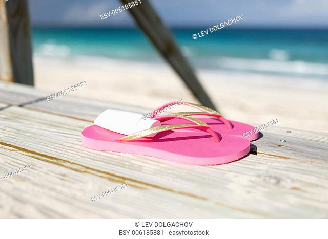 beach, summer, vacations and accessories concept - close up of sunscreen and slippers at seaside