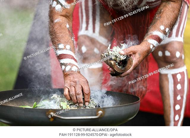 28 November 2019, Saxony, Leipzig: Major Sumner, representative of the Australian Ngarrindejeri Community, conducts a smoking ceremony in the courtyard of the...