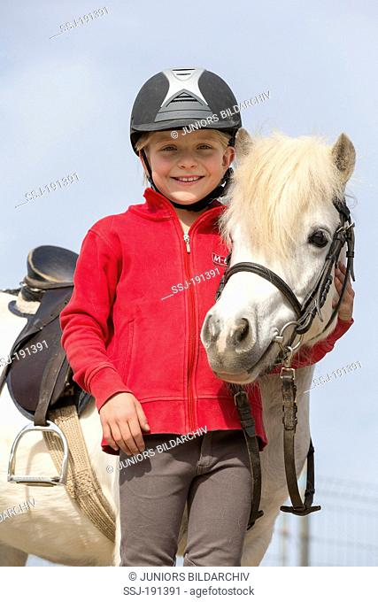 Shetland Pony. Girl holding gray pony on rein. Germany