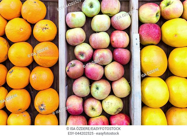 apples, grapefruits and oranges are sold in wooden crates on market stall