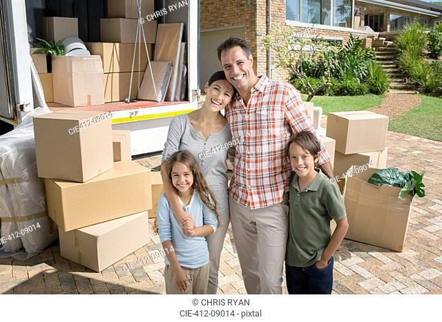Portrait of smiling family standing near moving van in driveway