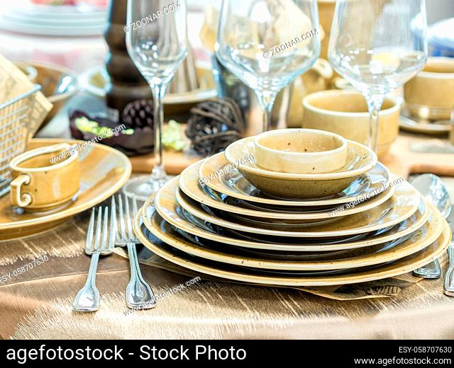 Set of new dishes on table with tablecloth. Stack of beige plates and wine glasses on restaurant table. Shallow DOF