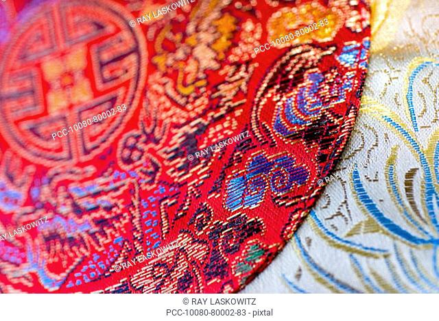 Close-up of bright red cloth over white cloth with Chinese embroidery