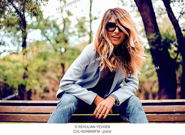 Stylish woman with long blond hair wearing sunglasses sitting on park bench, portrait