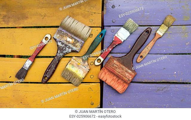 set of used brushes with bits of dried paint on colored wood background