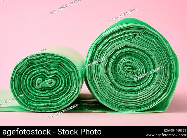 two rolls green plastic bags for trash bin on pink background, close up