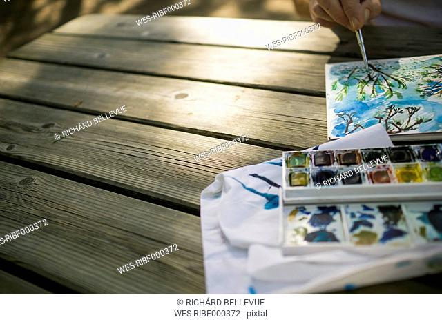 Woman painting on wooden table outdoors