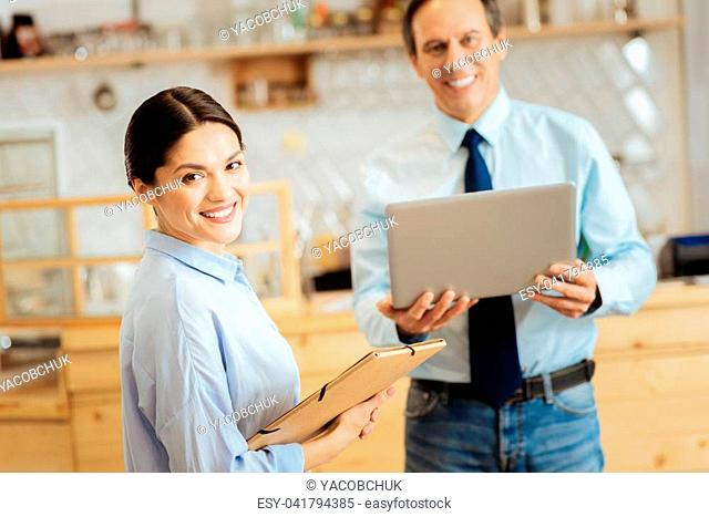 Reliable partner. Confident nice-looking pretty woman standing in the bright room near a man looking straight and holding the folder