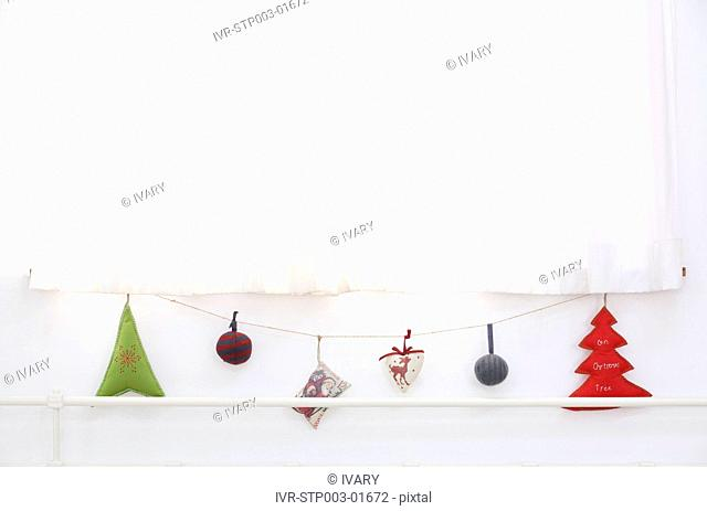 Christmas Ornaments Hanging On String Near Window