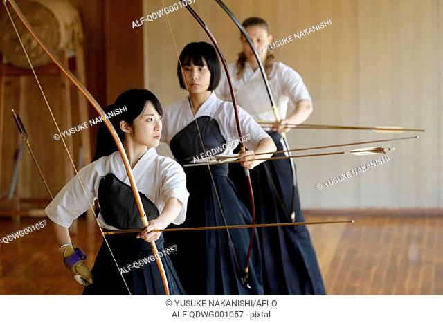 Multi-ethnic group of traditional archery athletes practicing