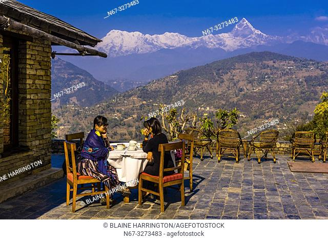 Chinese tourists enjoy the view of the peaks of the Annaupurna Massif of the Himalayas from Tiger Mountain Pokhara Lodge, Lekhnath (near Pokhara), Nepal