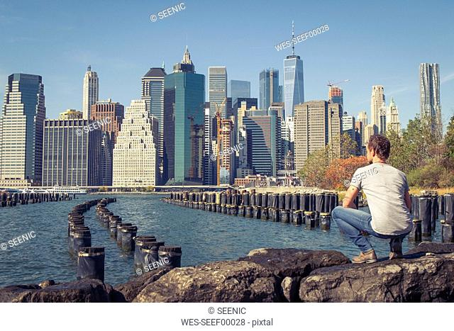 USA, New York City, man looking at skyline with One World Trade Center