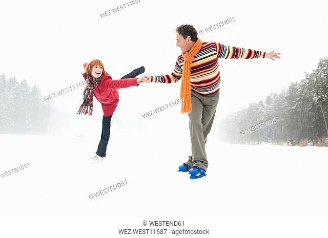 Italy, South Tyrol, Seiseralm, Woman ice skating on one leg, Man assisting
