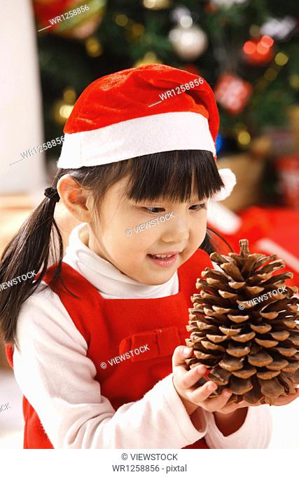 Girl holding pinecone at Christmas
