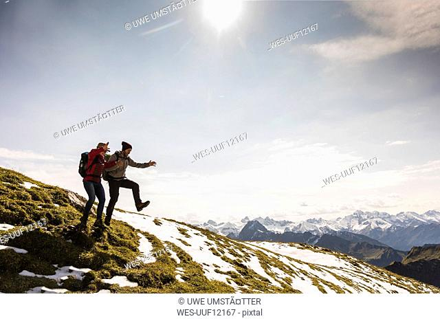 Germany, Bavaria, Oberstdorf, two hikers jumping on alpine meadow