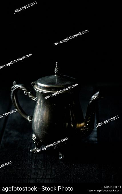 Teapot of silver in front of black background