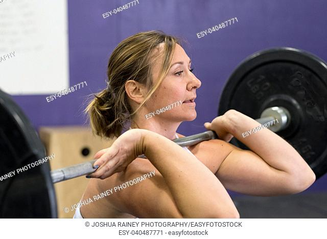 Fit young woman lifting weights at a crossfit gym