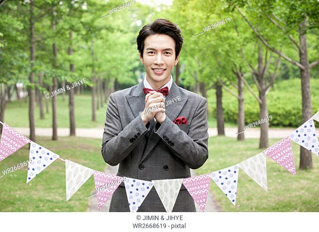 Portrait of young smiling groom holding hands outdoors