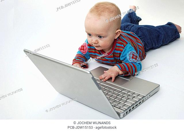 Six month old baby boy working on a laptop computer