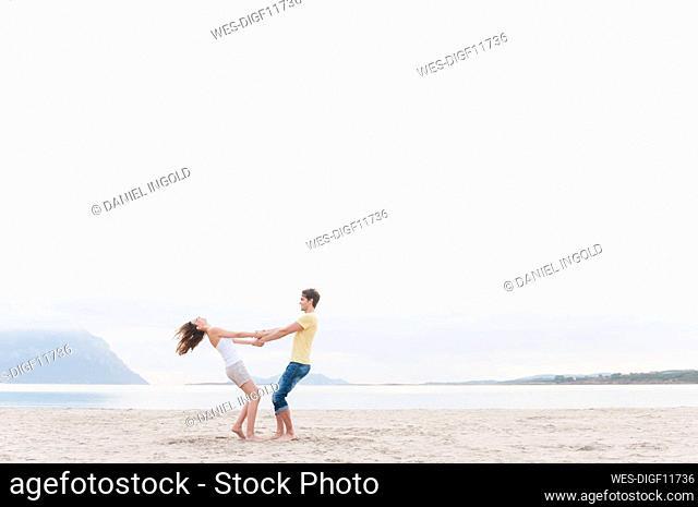 Happy couple having fun together on the beach, Sardinia, Italy