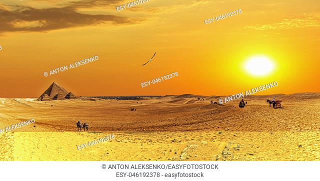 Giza desert panorama with the Great Pyramids and bedouins