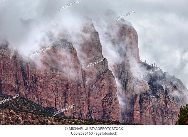 A passing thunderstorm deposits clouds around Mount Kinesava at Zion National Park, Utah