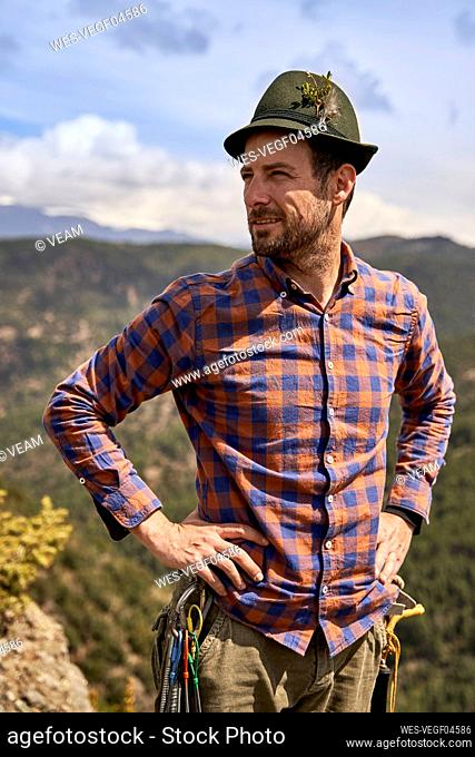 Mid adult male mountaineer standing with hand on hip during sunny day