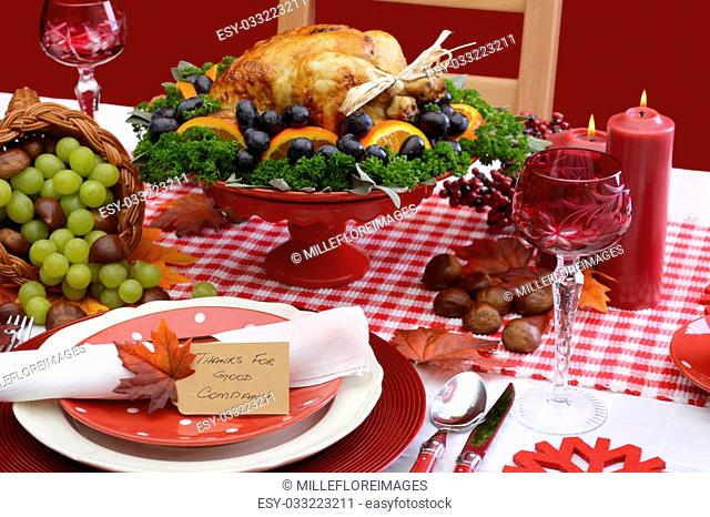 Red and white theme Thanksgiving table with individual place setting, food and cornucopia