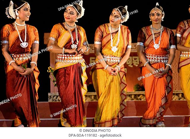 Odissi dancers in mythological scene against backdrop of world heritage Sun temple complex in Konarak ; Orissa ; India MR400
